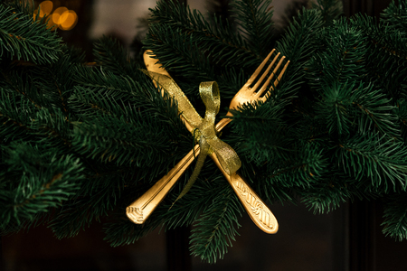 stylish luxury  golden knife and fork on christmas wreath, creative celebration decoration for holidays in the city