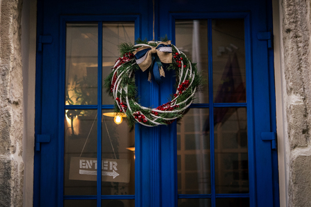 stylish amazing christmas wreath on blue door, celebration decoration for holidays in the city