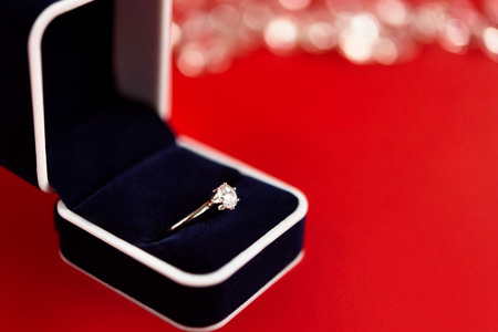 stylish luxury ring with diamond in blue box on red background, present and love concept