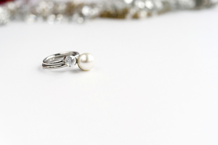 expensive: stylish luxury rings with pearl and diamond on white background, space for text, love gift concept