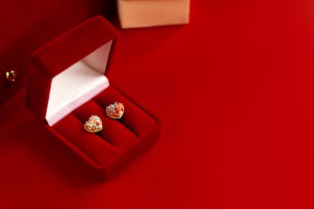 stijlvolle luxe hart oorbellen met kleurrijke edelstenen op rode achtergrond, Valentijnsdag concept