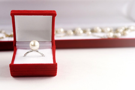 stylish pearl ring and necklace in red box on white background, valentines day gift concept