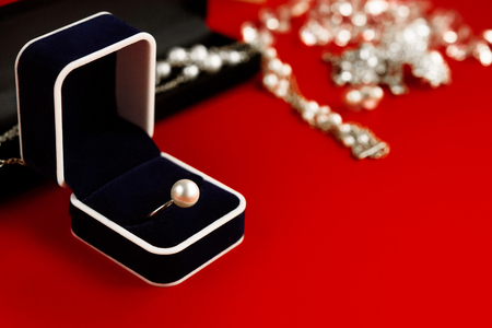 luxury ring and stylish necklace and gift box on red background, present and love concept, valentine's day