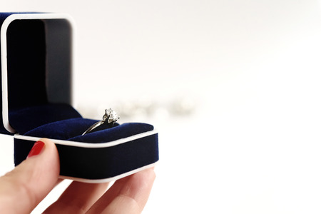 stylish luxury ring with diamond in blue box in hand on white background, present and love concept, valentines day proposal