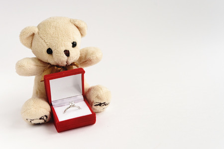 stylish luxury ring with diamond in red box and teddy bear on white background, valentines day concept