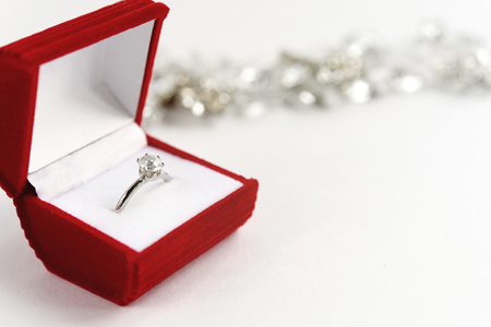 platinum: stylish luxury ring with diamond in red box on white background, present and love concept, valentines day