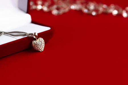 luxury heart necklace with stylish diamonds on red background, present and love concept, valentines day