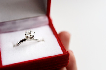 platinum: luxury ring with diamond in stylish red box in hand on white background, present and love concept, valentines day proposal Stock Photo