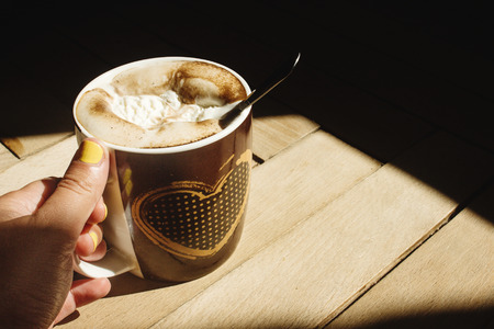 delicious aromatic  brewed whipped with icecream coffee in a brown cup with a heart in a hand and sunlight in the morning on the background of a wood Stock Photo