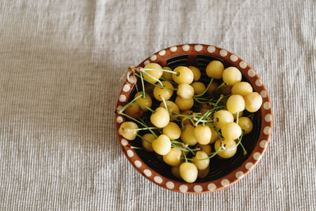 table top: delicious yellow cherries in old bowl on rustic background, top view, summer concept, space for text