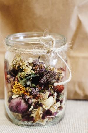 mooie gedroogde bloemen, verschillende smaken, in glazen pot op rustieke achtergrond van ambacht