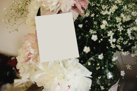 blank empty card for greeting simple text  on background of bouquet of  peonies