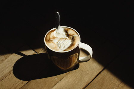 delicious aromatic  brewed whipped with icecream coffee in a brown cup with a heart in a sunlight in the morning on the background of a wood