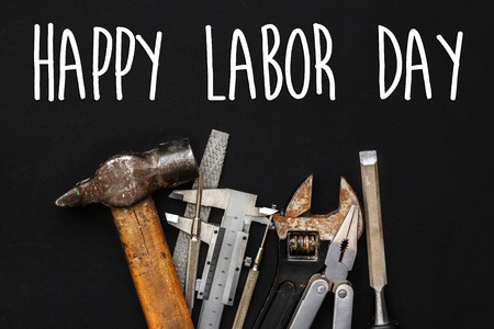 happy labor day text sign. Working tools on black background. set instruments for hand work and fixing. Construction and renovation concept flat lay, copy space.