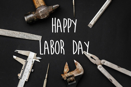 happy labor day text sign. Tools for repairing and renovation concept on black background top view. Working tool set and instruments for fixing flat lay, copy space Stock Photo - 84490869