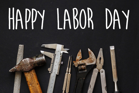 happy labor day text sign. Working tools on black background top view. set instruments for hand work and fixing. Construction and renovation concept, copy space. Stock Photo
