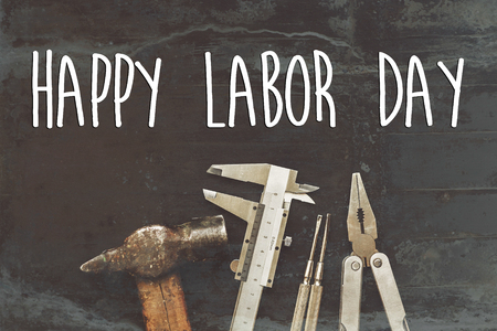 happy labor day text sign. Working tools on black background top view. tool set and instruments for hand work and fixing. Construction and renovation concept flat lay with copy space.