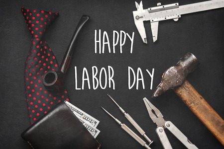 happy labor day text sign concept flat lay. working tools, bow tie leather wallet with money wooden tobacco pipe and razor on black background with space for text, top view. greeting card Stock Photo