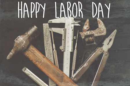 happy labor day text sign. Tools for repairing and renovation concept on black background top view. Working tool set and instruments  flat lay, copy space