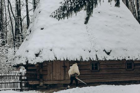バイキング戦士の戦い、ヴァルハラから戻ってきた冬の北の森で歴史的な木造建築に向かって歩いて剣とオオカミの毛皮と強いバイキング ファンタ 写真素材