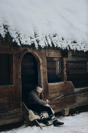 スカンジナビア、モホーク、ファンタジーのコスプレ コンセプトの戦い前に武器とポーズでハンサムなバイキングで冬の森の建物歴史的の木城付近