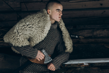 Strong, angry viking warrior with axe before battle at war, ancient scandinavian warrior cosplay, thor costume, northern lumberjack costume, confident facial expression of  man near wooden building