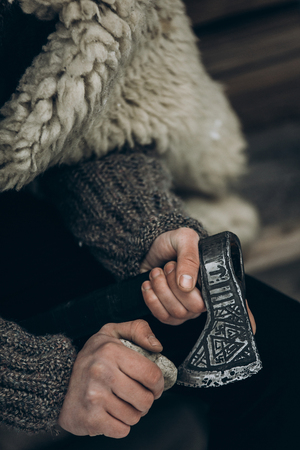 Northern warrior with weapon, viking sharpening his axe before battle hands close-up, scandinavian lumberjack with steel axe, viking costume cosplay, norway historical heritage concept Stok Fotoğraf