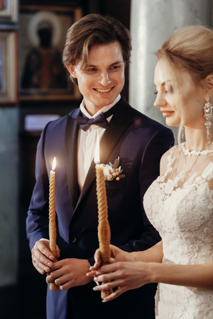 Beautiful bride and groom holding candles during wedding ceremony in church, gorgeous blonde bride and handsome groom performing spiritual ritual, marriage concept Stock Photo