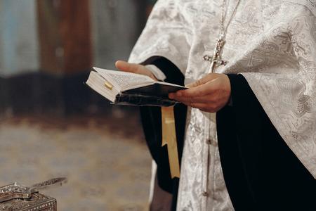 Priest reading holy bible in christian church during orthodox wedding ceremony, spiritual ritual concept Zdjęcie Seryjne - 84725261