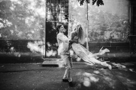 Stylish hipster couple dancing in the street of Paris, happy man swirling his woman in air, strong husband twirling with his wife Stock Photo - 84785449