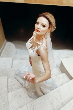 Gorgeous bride in sexy white wedding dress posing on marble staircase indoors, beautiful blonde bride portrait on stairs in elegant dress Stock Photo