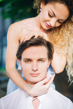 Beautiful blonde woman in blue hipster dress caressing handsome man with stylish haircut, newlywed couple portrait, mans face closeup