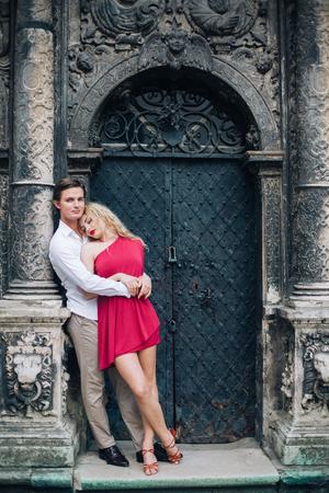 ハグの新婚旅行、パリの大聖堂に近いセクシーな赤でゴージャスな金髪女性のロマンチックな新婚カップル ドレス スタイリッシュなシャツ、家族の