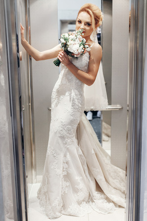 Gorgeous bride in hotel elevator, beautiful female bride in elegant white wedding dress posing in elevator with wedding bouquet, morning preparation concept