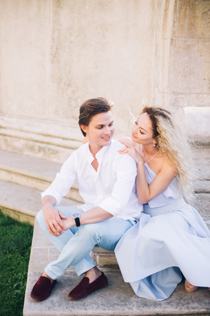 Happy, sensual couple relaxing on stone stairs in France, smiling hipster woman in blue dress touching handsome man in white shirt and loafers