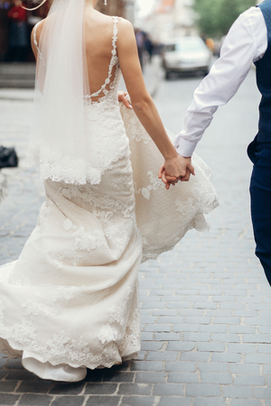 holding hands while walking: Elegant couple of newlyweds holding hands while on a walk in the city after the wedding ceremony, gorgeous blonde bride walking with handsome groom