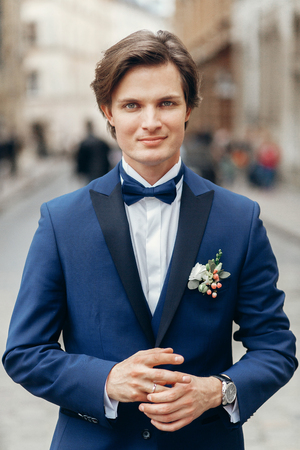 Handsome groom portrait, smiling groom in elegant blue suit with boutonniere posing outdoors close-up, man wedding fashion concept