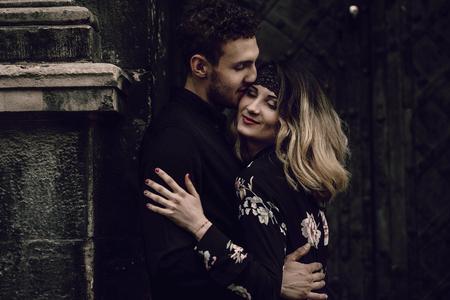 stijlvolle zigeuner paar verliefd zoenen in avond stadsstraat op oude gebouw. vrouw en man omarmen, romantisch Frans atmosferisch moment. hou van je humeur. ongebruikelijke bruid en bruidegom