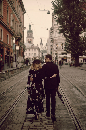 stylish gypsy couple in love walking and hugging in evening city street. woman and man gently embracing, romantic french atmospheric moment. love mood. back view
