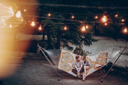 Romantisch hipster paar geniet van rust op een hangmat bij park resort, schattige vrouw liggend met knappe man, lichten op de achtergrond Stockfoto