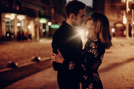 stijlvolle zigeuner paar verliefd knuffelen en kussen in avond stadsstraatjes. vrouw en man omarmen, romantisch Frans atmosferisch moment. gepassioneerde liefdesstemming. sensuele aanraking