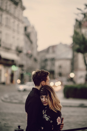 stylish gypsy couple in love hugging in evening city street at moving car lights. woman and man embracing, romantic french atmospheric moment. passionate love mood.