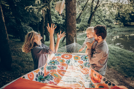 Young family playing with son on a hammock in park on camping trip, hipster mother putting a vintage hat on a baby boy near handsome father holding him, family vacation Archivio Fotografico
