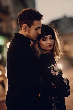 stylish gypsy couple in love hugging in evening city street car lights. woman and man embracing, romantic french atmospheric moment. passionate love mood. sensual touch