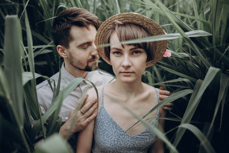 hipster couple posing at lake in cane in summer forest. stylish rustic bride and groom, girl in fashionable modern dress and straw hat with peony, embracing in windy high reed. rustic wedding concept Stock Photo