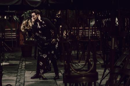 stijlvolle zigeuner paar verliefd hartstochtelijk dansen in avond stadsstraat op cafe terras. vrouw en man kussen, romantisch frans atmosferisch moment. passie hou van stemming.