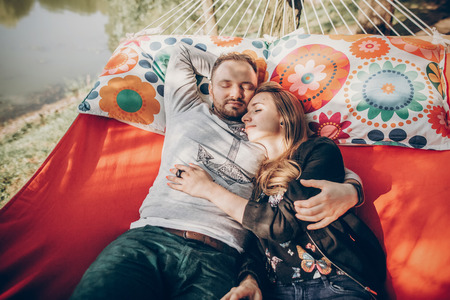 Cute married couple sleeping in a comfortable hammock outdoors near a lake, handsome man hugging woman while relaxing on vacation