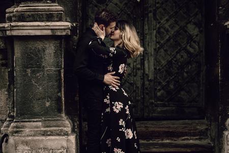 Het elegante romantische paar kussen dichtbij oude metaalpoort in Parijs, mooie blondevrouw die de gebaarde mens in openlucht, hartstochtsconcept koesteren Stockfoto