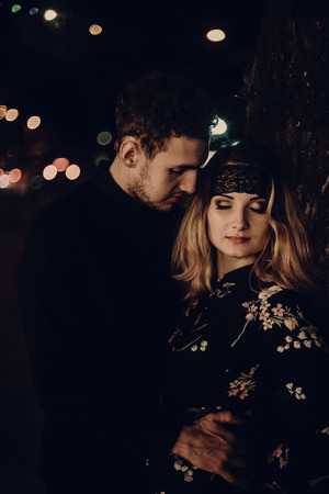 passionate lovers embracing in evening city street. stylish couple in love gently hugging in city lights. modern woman and man romantic french atmospheric moment.