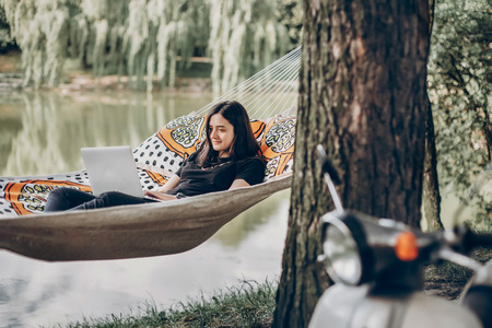 Young female freelancer working on laptop while lying on a hammock near a lake, hipster woman resting in nature near retro italian motorcycle Archivio Fotografico